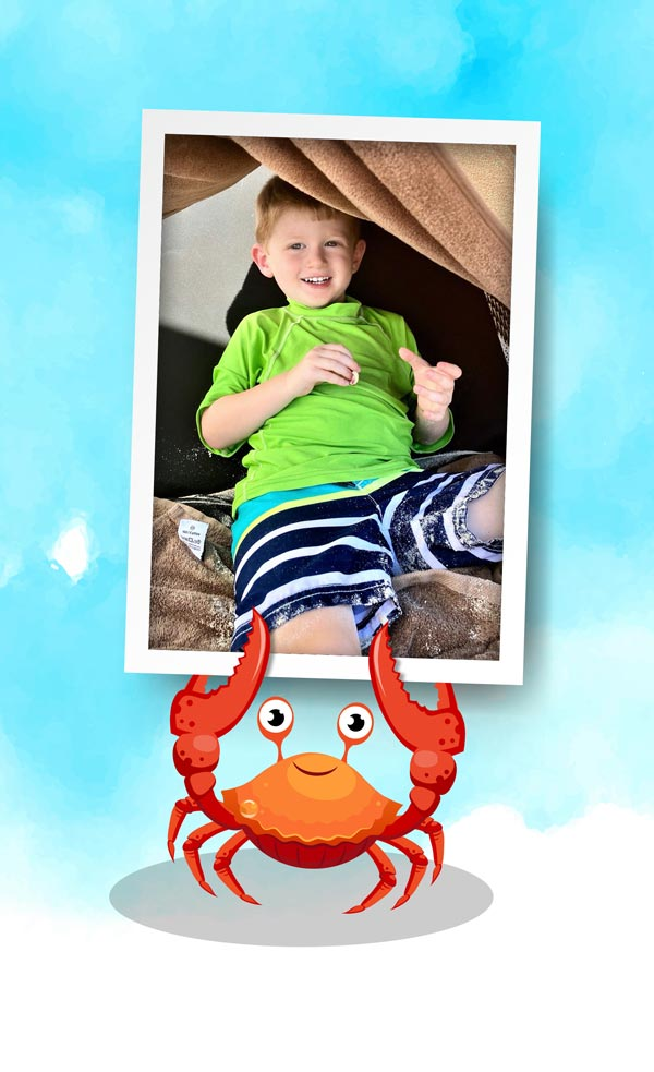 A picture of a boy (Jax) on a beach towel, held by a crab