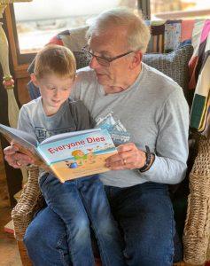 Pops reading Jax the book Everyone Dies